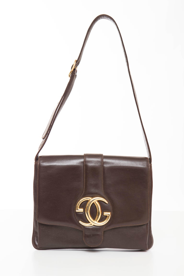 Gucci 1970's brown leather handbag with fold over top flap, gucci gold logo hardware, adjustable strap and two interior compartments with one zip deep pocket.  Serial Number: MOD.BREV 53289  Height 8, Width 10, Depth 1, Shoulder Strap Adjust To 13 -