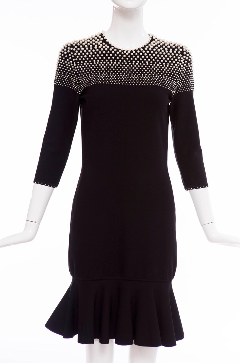 Alexander McQueen Autumn-Winter 2013, black long sleeve knit dress with round neckline, faux pearl embellishments at top throughout, embellished trim at sleeve opening, flared hem and keyhole at center back featuring button closure at nape.  Bust