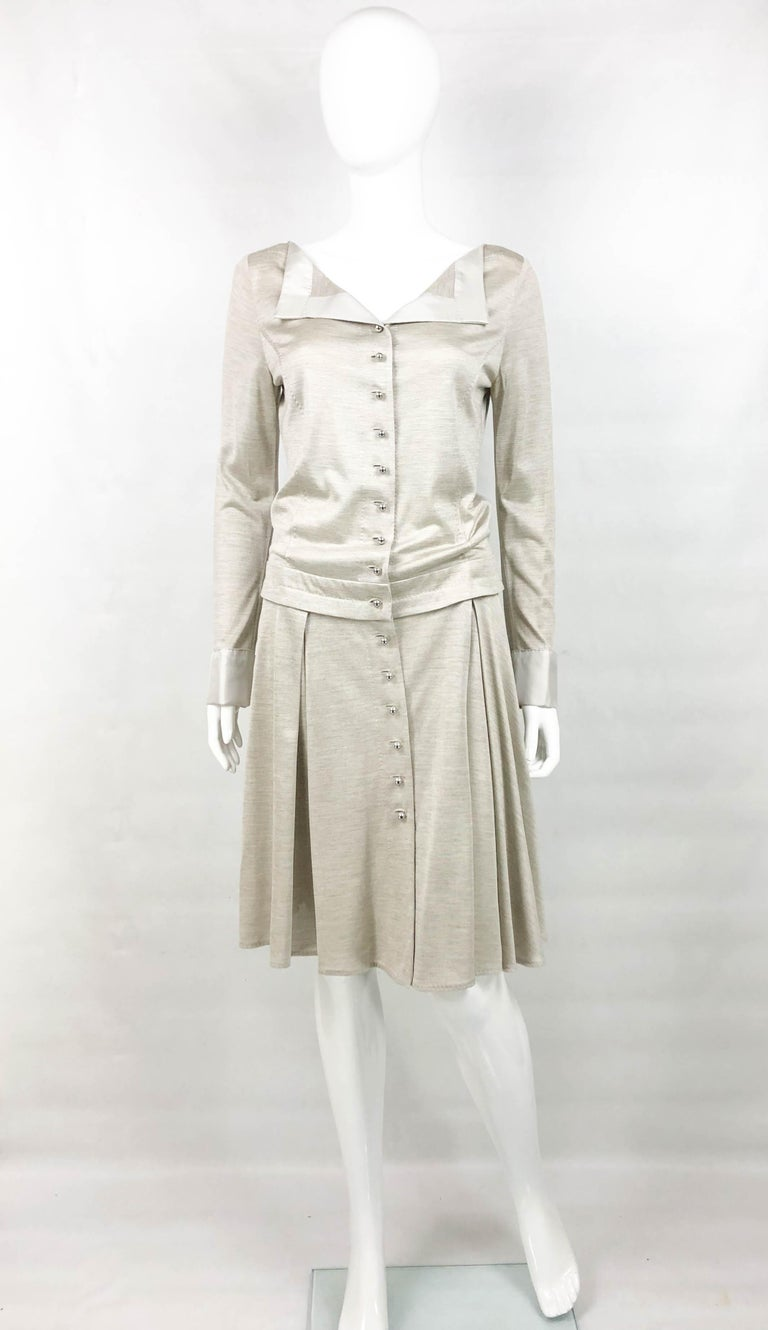 This stylish shirt dress by Louis Vuitton is made in silk jersey. With long sleeves and dropped waist, it hovers at knee height. The cuffs and lapel are made in silk. The silver-tone buttons are round and read Louis Vuitton. The cuffs come adorned