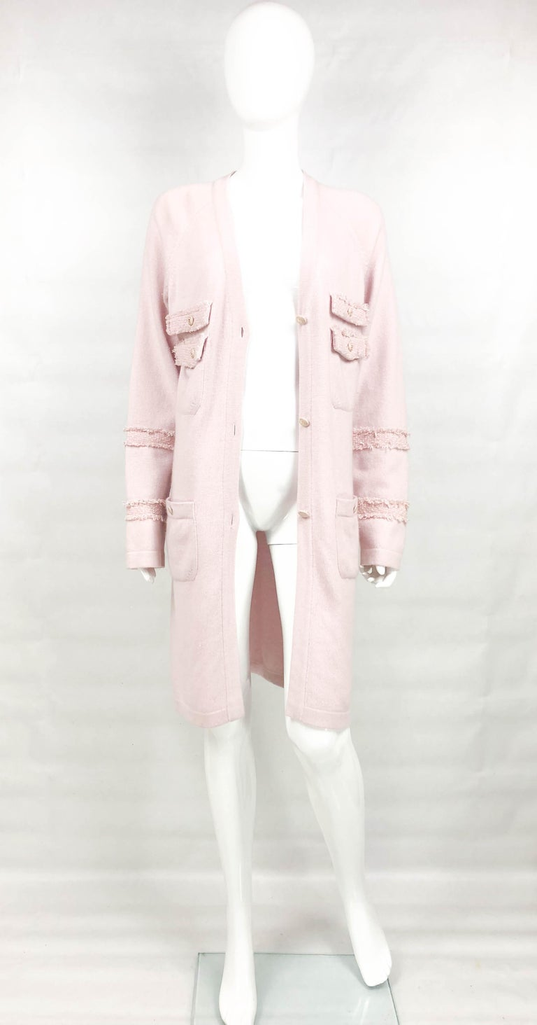 Chanel Pink Cashmere Cardigan Dress. This beautiful piece by Chanel was created for the 2009 Fall / Winter Collection. Made in light pink cashmere, this cardigan dress hovers at knee height. There are 4 square pockets on the front and distressed