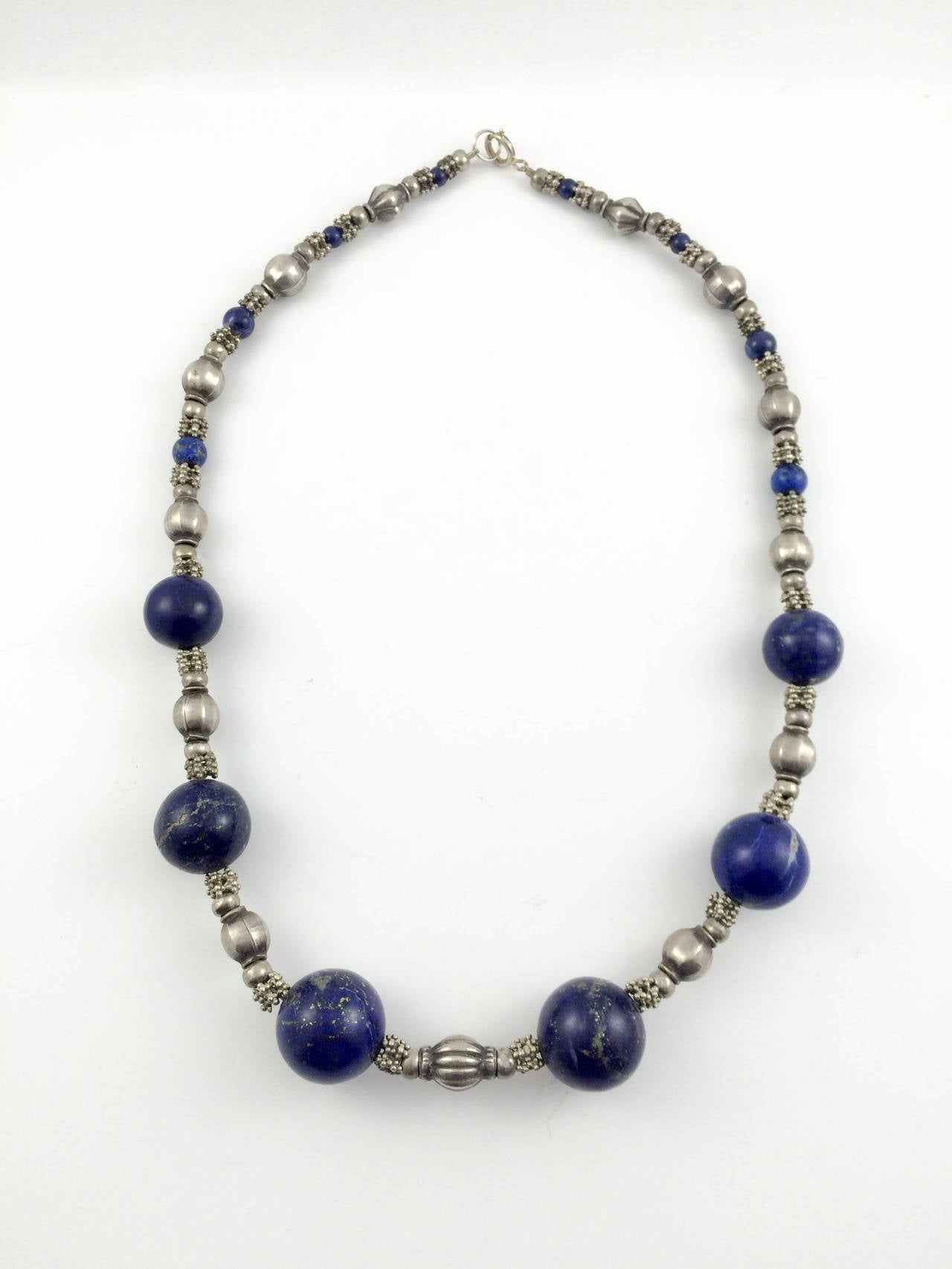 Stylish Vintage Silver and Lapis Lazuli Necklace. Intricate lovely design on silver with lapis lazuli beads. We are uncertain of its origins, but it has an Asian influence.    Period: 1970s  Materials: Silver and Lapis Lazuli  Condition:
