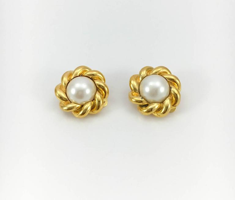 Chic Vintage Chanel Gold Plated Pearl Earrings. These very stylish earring by Chanel feature a cabochon glass pearl in the centre and twisted rims. Gold plated, they are Chanel signed and numbered (2180) on the back. In a vintage Chanel box.