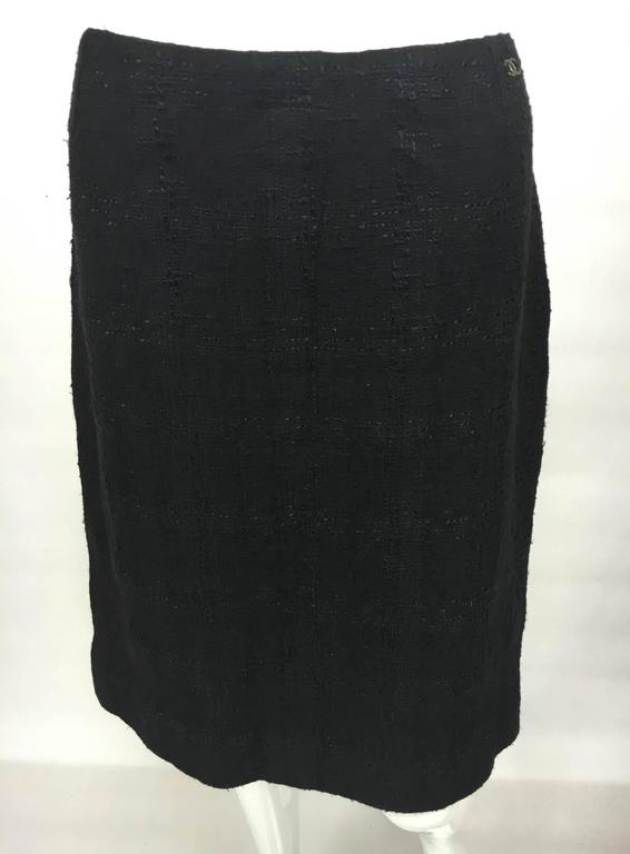 This stylish piece is a Chanel Black Boucle Skirt. Knee-length, it has a slit at the back. It features an invisible side zipper and the iconic Chanel 'CC' logo in metal at the waist. A bit of timeless class by Chanel.  Label / Designer: