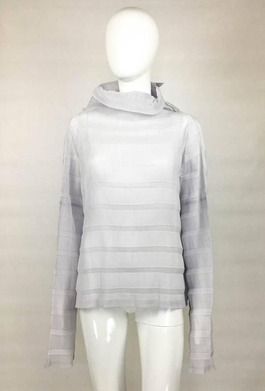 Edgy Issey Miyake Pleated Blouse. This wonderful top by Issey Miyake shows the fashion house classic pleats (heat-set-pleats technique). In pale lavender/lilac, the design is avant-garde featuring very long sleeves and dramatic roll neck, bringing
