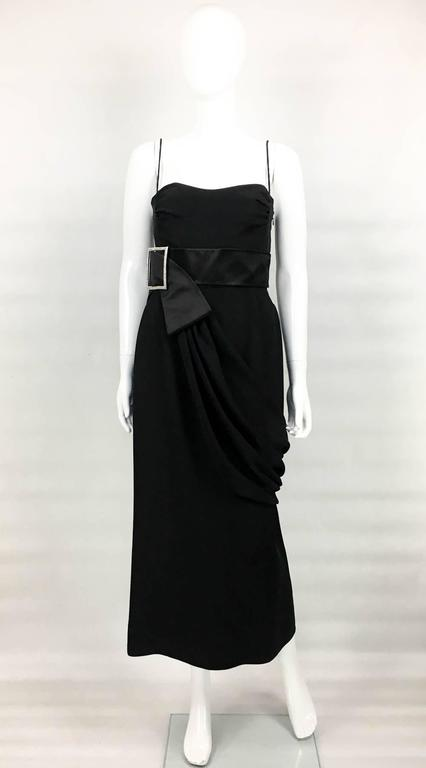 Chic Valentino Evening Dress. This stunning silk-blend dress by Valentino features a silver buckle with diamanté details on a satin sash and draping from the waist. It has an invisible side zipper and it is lined from the waist up. The silhouette