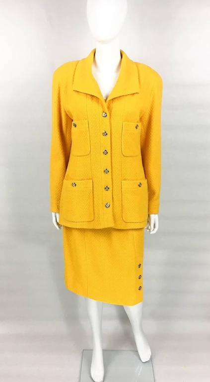 Striking Vintage Chanel Wool Skirt Suit. This wonderful ensemble by Chanel dates back from the early 1980s. Made in a beautiful tone of golden yellow wool bouclé, this suit is certain to steal the spotlight. The jacket features four front pockets