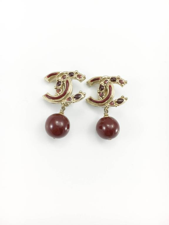 Gorgeous Chanel Red Gripoix Logo Earrings. These striking dangling clip-on earrings by Chanel are from the 2012, specifically from the Paris-Bombay Collection. In this collection, Karl Lagerfeld brought a poetic idea of India, a Parisian mixture of