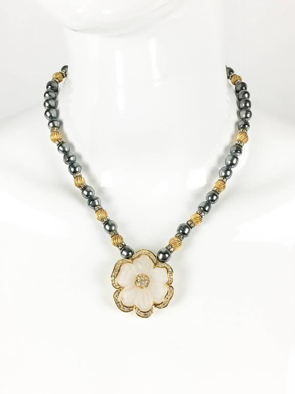 Beautiful Dior Vintage Flower Necklace. This stylish piece by Dior dates back from the 1990's. It features grey faux pearls, textured golden beads, spaced by paste/rhinestone embellished rings. The main aspect of this necklace is the flower pendant
