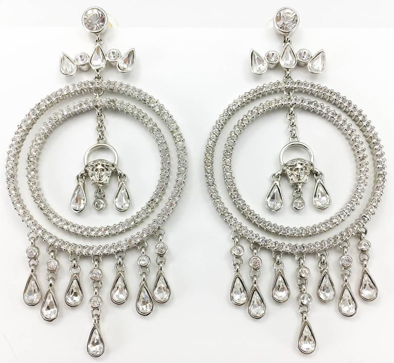 Fabulous Versace Chandelier Earrings. These amazing earrings by Versace are truly show-stoppers. In white metal, they feature 2 diamanté encrusted hoops, various dangling teardrop-shaped crystals and Versace's trademark, the iconic 'Medusa's Head'