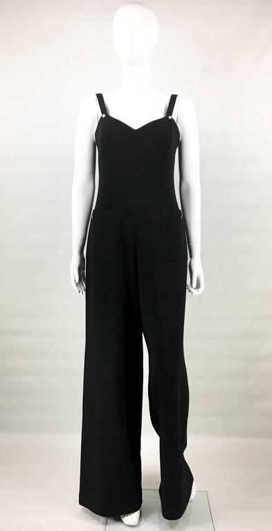 Vintage Chanel Black Wool Jumpsuit. This chic piece by Chanel dates back from 1995, more precisely the Spring/Summer collection. Made in a light wool fabric, and lined in silk, this loose-fit jumpsuit features dungaree-style buttoned shoulder straps