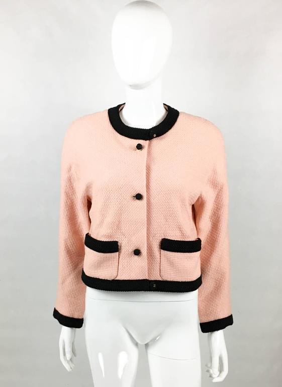 Vintage Chanel Pink Tweed Jacket. This beautiful jacket by Chanel was created in the 1990's. In pink tweed, it features black knot buttons and black cord trims to the collar, hemline, cuffs and pockets. The buttons on the collar and hemline have a