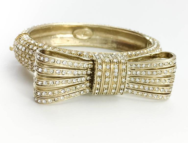 Vintage Valentino Gilt Diamanté Bow Bracelet. This stylish bracelet by Valentino dates back from the 1980's. In gilt metal, it features a bow on top, and all the outer surface is rhinestone embellished. Valentino marked on the inside. This is a