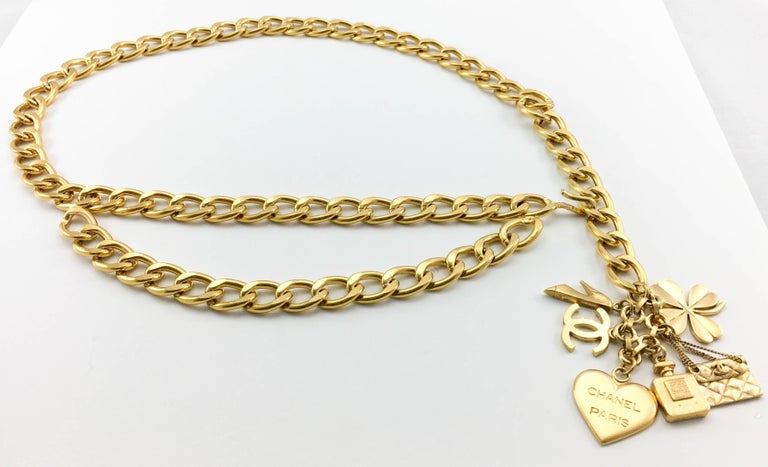Vintage Chanel Gilt Chain With Charms Belt. This fabulous belt by Chanel was created for the 1996 Spring / Summer Collection. It is made in a chunky gilt metal chain with a 2-tier design on the front. The main feature, however, must be the charms at
