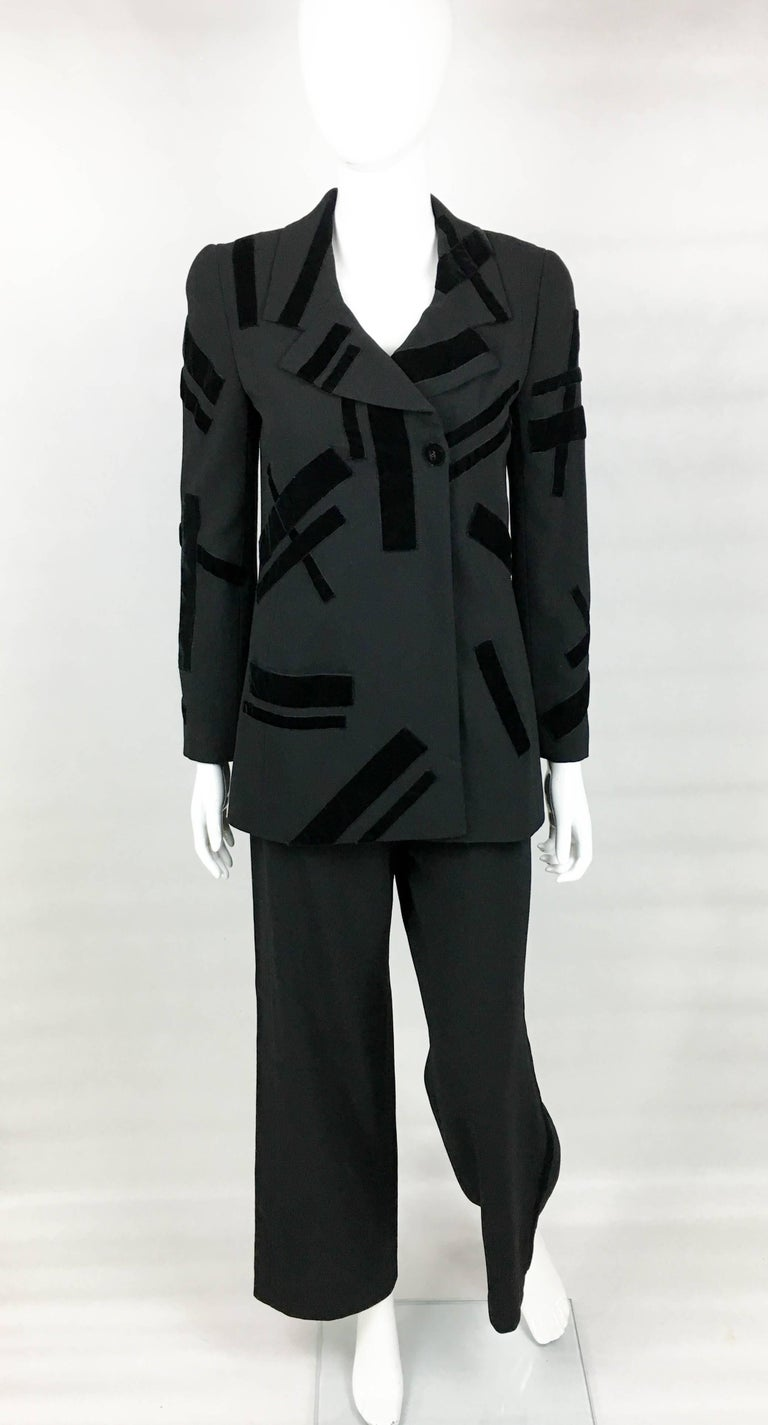 Vintage Chanel Black Trouser Suit with Velvet Details. This stylish suit by Chanel dates back from 1998. Made in light wool, it is lined in silk. The jacket is lined in silk, has two pockets and various geometrically shaped velvet details. The