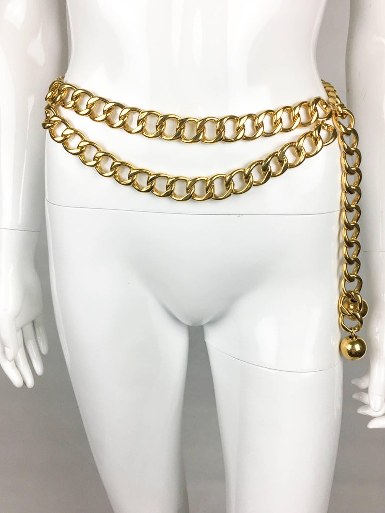 Vintage Chanel Gilt Chain Belt. This striking piece by Chanel dates back from the 1980's. Comprising of a chunky gilt chain, it features a double row on the front and a single row on the back. There are 2 gilt balls hanging on the end of the chain.