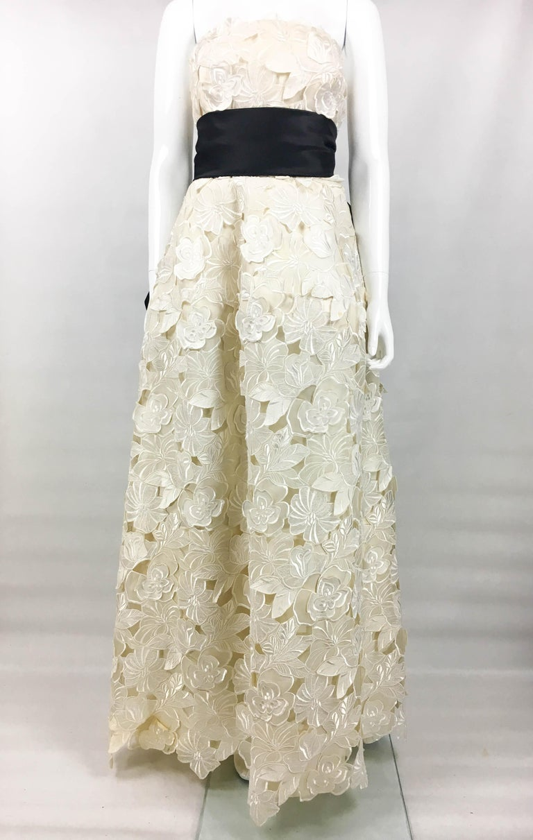 Vintage Givenchy Haute Couture Off-White Evening Gown. This stunning gown by Givenchy was crafted in 1985. Made in silk, it is over-layered with jacquard and embroidery flowers. The sleeveless design has a full floor-length skirt. Internally, it is
