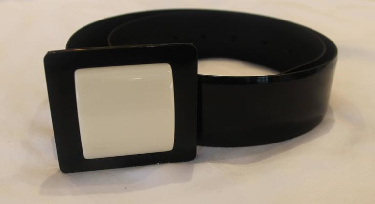 Chanel Black Patent and Ivory Colored Square Buckle Belt - 36 - 2007 A. This was a runway piece. This black patent Chanel belt features a black buckle with an ivory colored plastic square inside. The buckle has the word