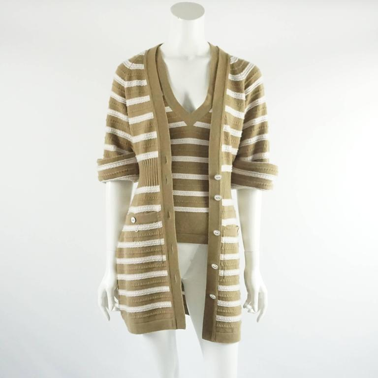 This classic Chanel set is a striped camel and ivory cashmere. The set comes with a sweater dress that can be worn both ways. It has a textured fabric, cinched waist, ivory enamel buttons, 2 front pockets, and rolled sleeves attached with a stitch.