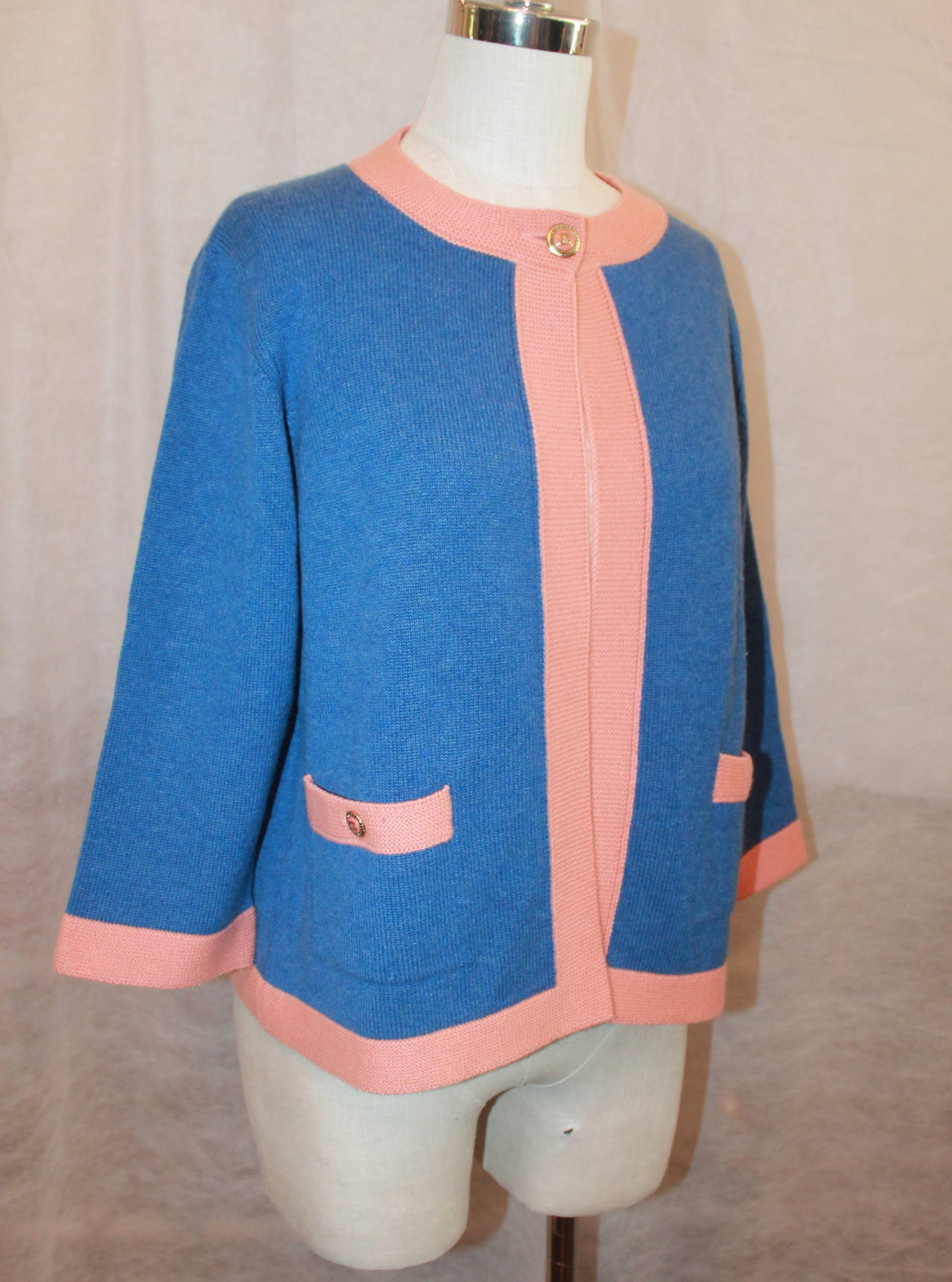 Chanel 2007 Blue & Peach Cashmere Sweater - 46. This round-neck sweater has a 3/4 sleeve and a single button at the top for closure. It also has 2 pockets on the side and is 100% cashmere. It is in excellent condition.