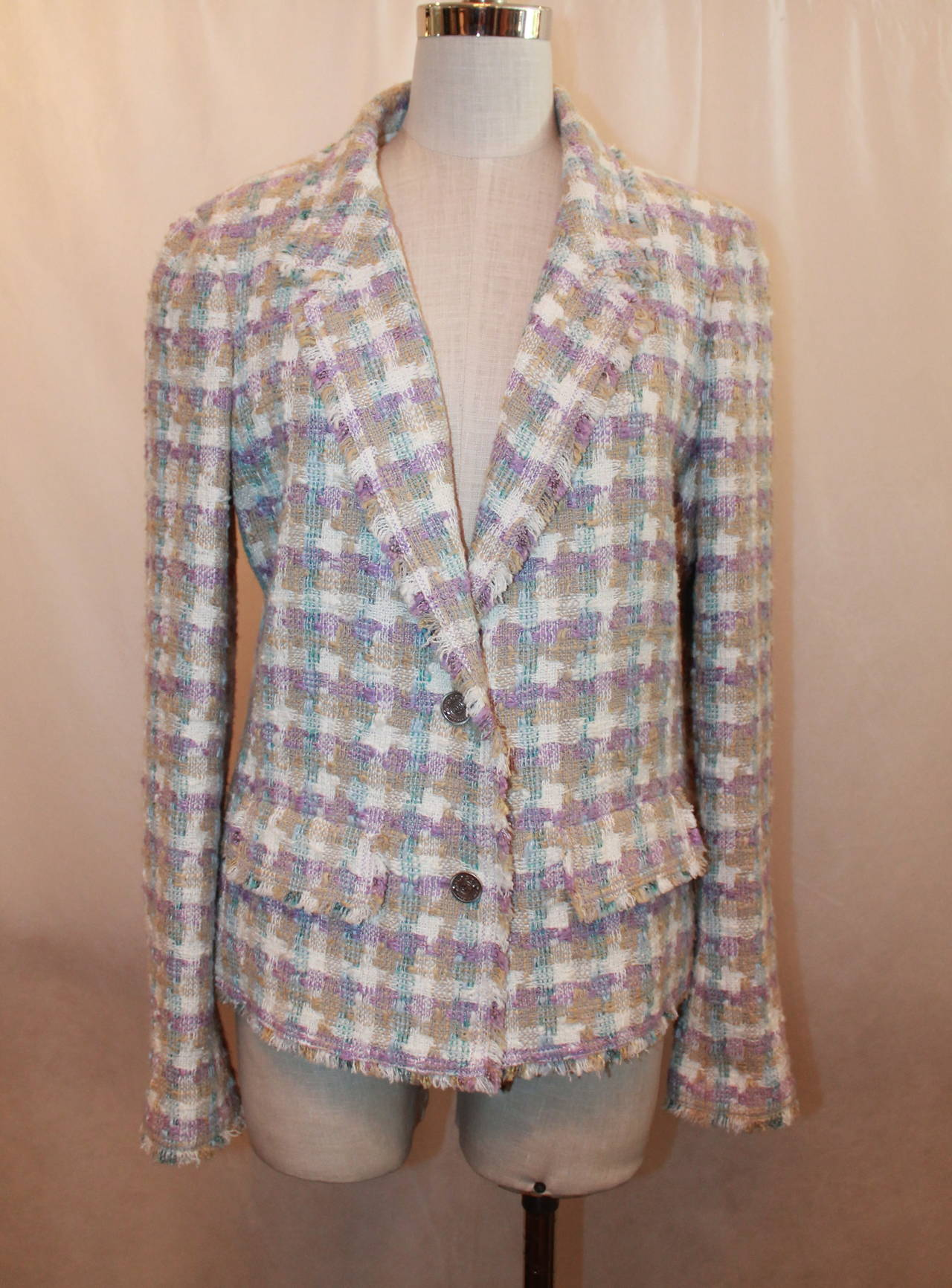 2005 Chanel White, Beige, Purple, and Blue Pastel Tweed Jacket with Two Front Pockets (Closed) and Coco Mademoiselle Button.  Fabric: 65 % Cotton 14 % Linen 14 % Viscose/Rayon 5 % Silk 2 % Nylon Lining: 96 % Silk 4 %