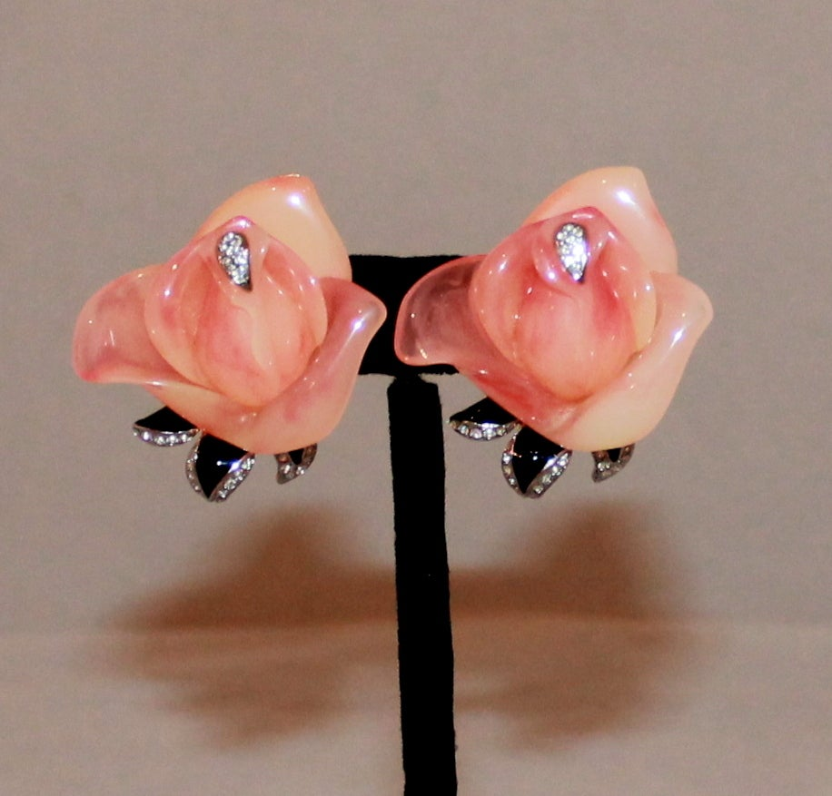 Kenneth Jay Lane 1990's Peach Rose & Rhinestone Clip-ons. These earrings are in excellent vintage condition and are gold-tone. They have a rose shape which looks like a peach colored Lucite and has a black leaf with rhinestone details. 
