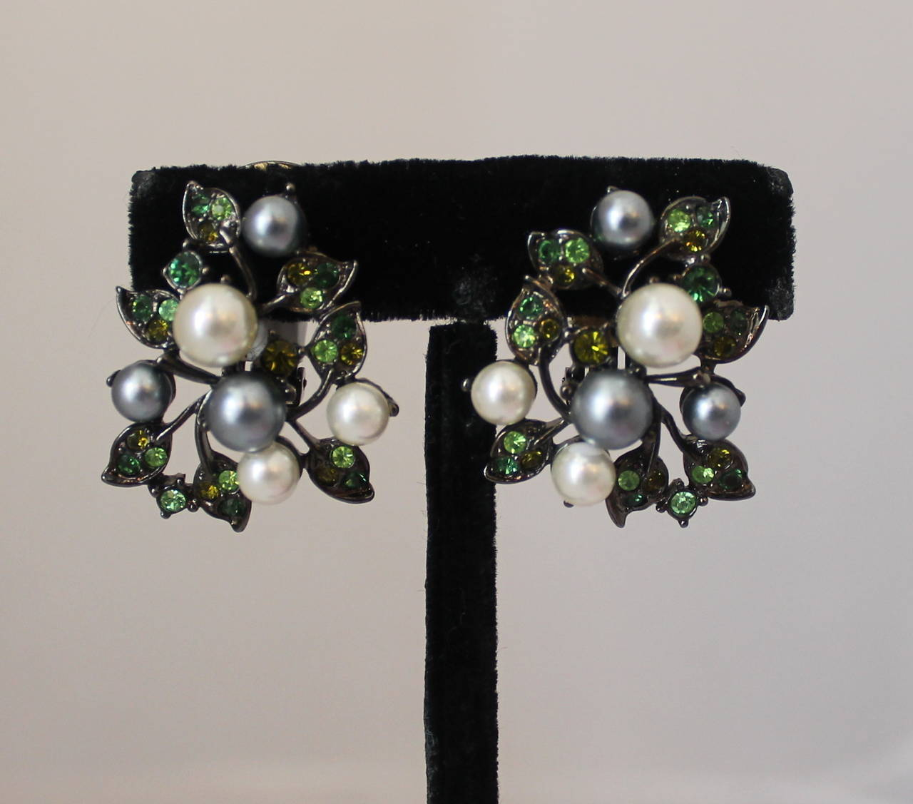 """Kenneth Jay Lane 1990's Pearl & Green Rhinestone Clip-on Earrings. These earrings are in excellent vintage condition and are a palladium tone. The pearls are ivory and grey while the rhinestones are lighter and darker green.   Length- 1.5"""" Width-"""