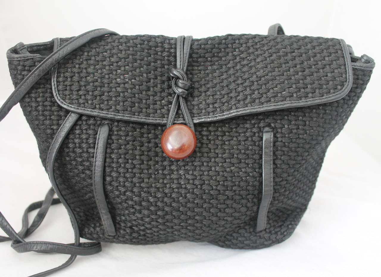 1980s Vintage Black Woven Raffia Crossbody Bag that can be Worn as a Backpack. Bag has Flap with Wood Button for Closure, Thin Leather Straps and Trim.  Measurements: Height: 9