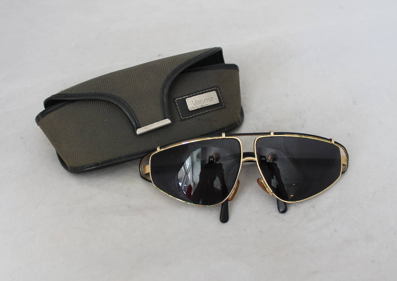 Versace 1980's Vintage Black & Gold Geometric Aviator Sunglasses. These sunglasses are in fair condition with a decent amount of wear due to their age. There are green markings along the gold seen on images 3-8. These sunglasses also come with a