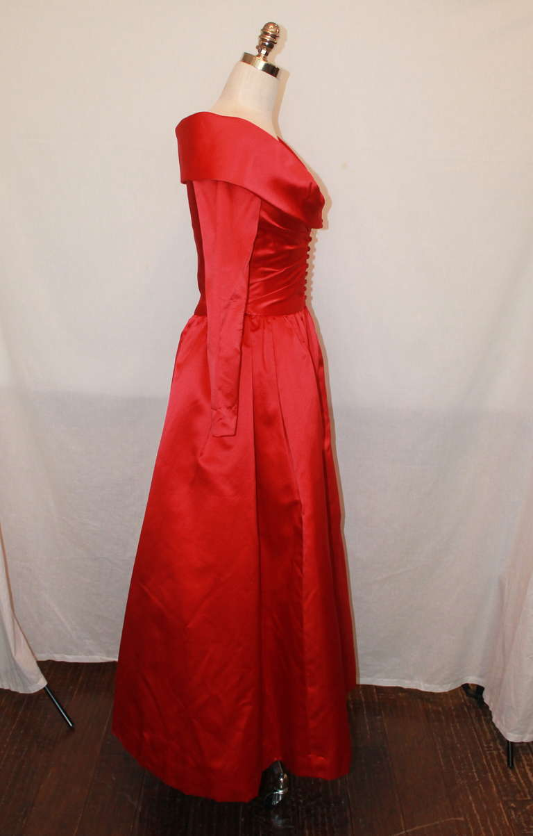 John Anthony red satin long sleeve gown. This gown has a portrait neckline with red jeweled buttons and is in excellent condition. Size 4.