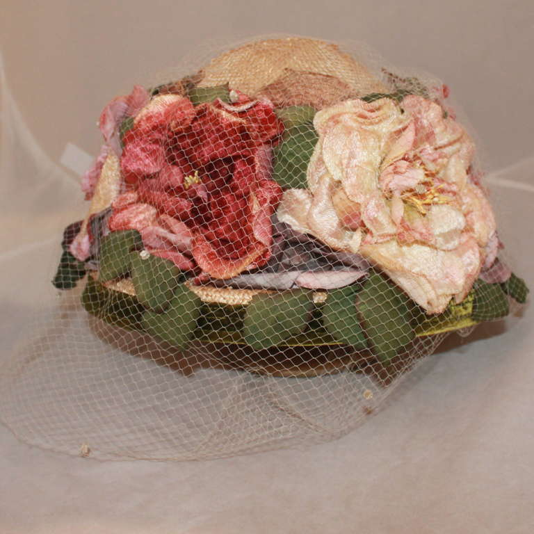 Kokin New York Flowered Hat with Pink and Red Flowers. This hat has a delicate veil and a green velvet trim. It is in impeccable condition. Measurements: Circumference- 22