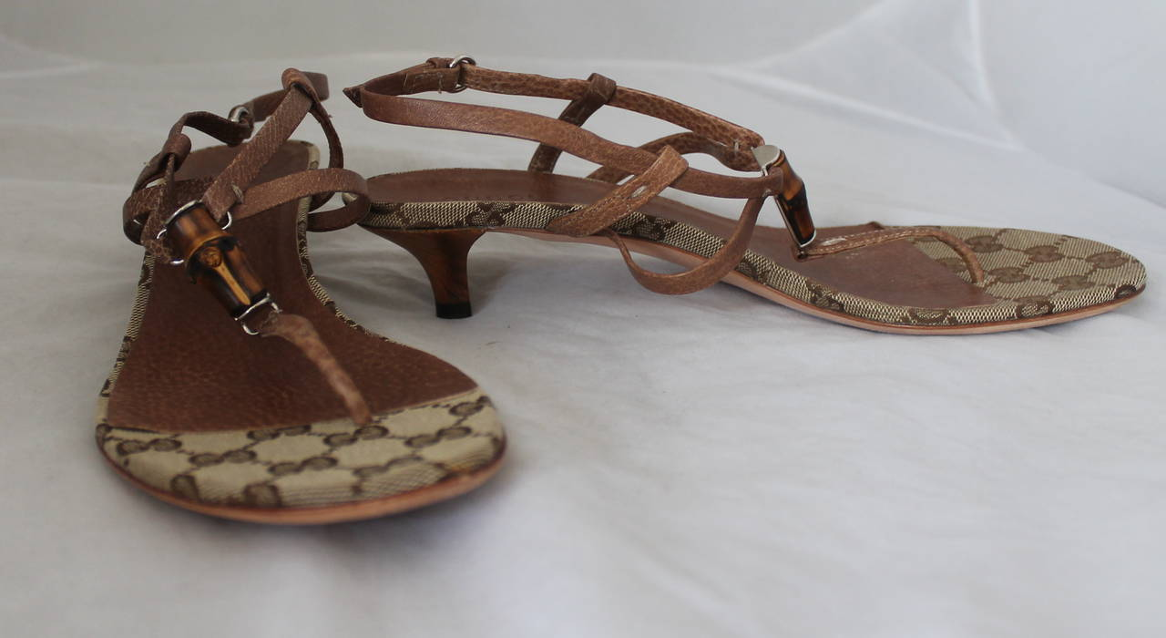 Gucci Brown Leather Thong Sandal with Bamboo Detail & Kitten Heel. These sandals are in fair condition with visible wear to the leather and bottom. It also has a Gucci monogram print on the bottom.