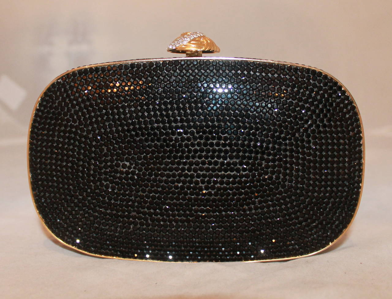Judith Leiber Vintage Black Crystal Minaudiere. This vintage piece is in excellent condition and has a longer strap. It has 3 stones missing one on side (one in the middle, two on the bottom portion), but other than that everything is impeccable.