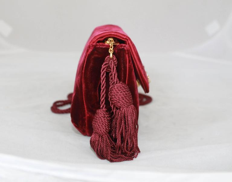 1990's Judith Leiber Vintage Burgundy Velvet Small Evening Bag. This beautiful bag features a double pope long strap and a tassel.  It has a gold medallion with white and red rhinestones.  It comes with a duster.  It is in excellent