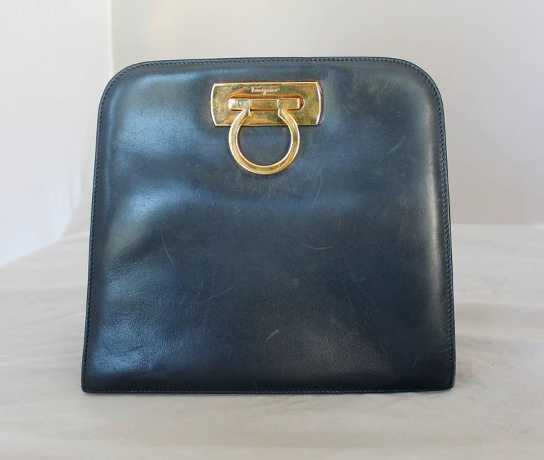 Salvatore Ferragamo Vintage Navy Leather Square Clutch/Crossbody Bag - GHW - Circa 80's  This bag is in fair condition with marks on the front, bottom, and back of bag. This bag is square shaped and has gold hardware with a gold chain. This bag