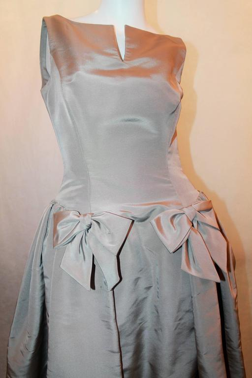 Oscar de la Renta Taupe Silk Taffeta Ball Gown - 12. This gown is in excellent condition with 2 front bows and a slit and the neckline. The torso is fitted and the gown has a drop waist with pleating all throughout. It is fully lined.