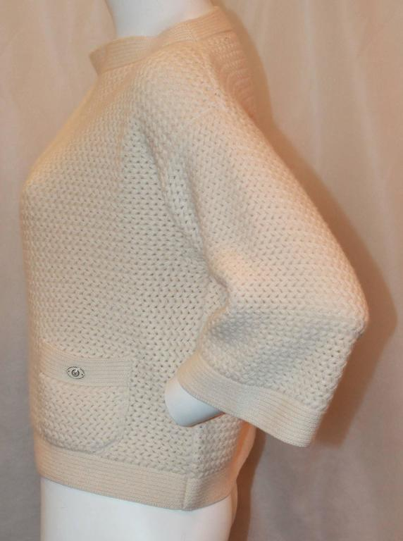 Chanel Ivory Cashmere Oversized Knitted Sweater Top - 42.  This simply beautiful sweater is in excellent condition.  It features two front pockets and an enamel Chanel logo on one of the pockets.  This sweater is absolutely gorgeous and incredibly