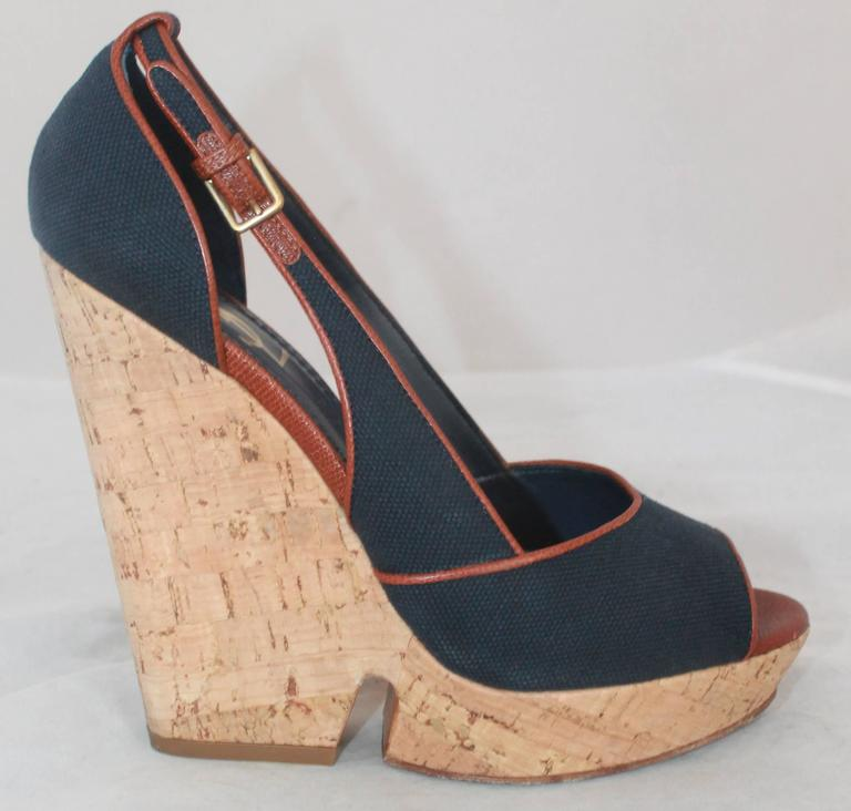YSL Navy & Brown Deuville Canvas Wedge Sandals - 40.5.  These sandals are in very good condition with only wear visible on the soles.  They feature navy canvas with a brown trim, an open toe, and a cork wedge with gold metallic