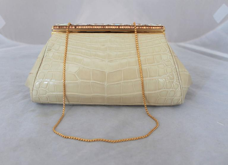 Judith Leiber Ivory Crocodile Clutch with Rhinestone and Gold Clasp. This piece is in excellent condition and has a longer gold strap. The inside lining is white leather. 