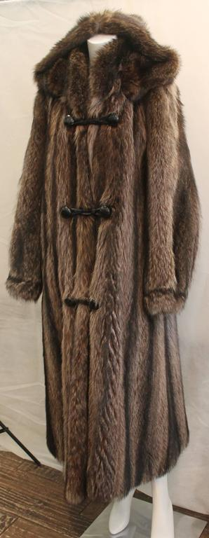 Custom Montgomery Style Hooded Brown Raccoon Full Coat - M. This piece is in excellent condition with the hood being detachable. It has front buttons with closure straps.   Measurements: Bust- 44