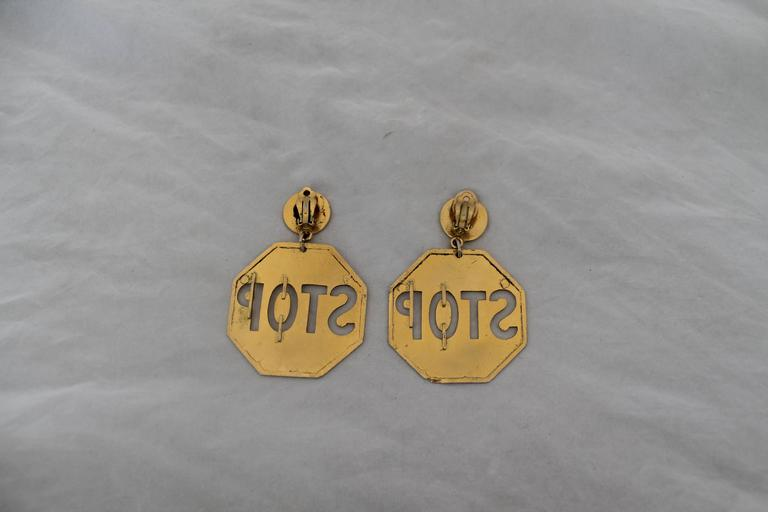 Moschino Vintage Goldtone Stop Sign Clip-on Earrings - circa 1980's. These earrings are in good vintage condition with wear on its color consistent with its age. The backs of one of these earrings has a brown coating on it. 