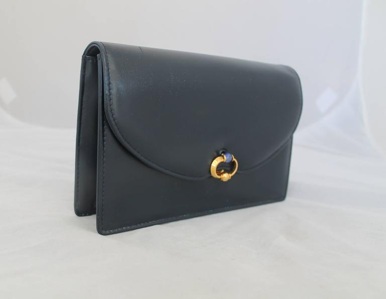 Gucci Vintage Navy Leather Clutch - GHW - Circa 1950's.  The beautiful vintage clutch is in excellent vintage condition.  It features a gold circular clasp and a blue jewel at center, a chic navy leather, a zipped compartment on the inside, and it