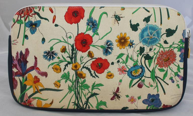 """Gucci Vintage Flora Canvas Clutch w/ Navy Leather Trim - GHW - Circa 1970's.  This adorable Gucci clutch is in good vintage condition with only some wear consistent with its age.  It features a classic """"Flora"""" garden design, navy leather trim, gold"""