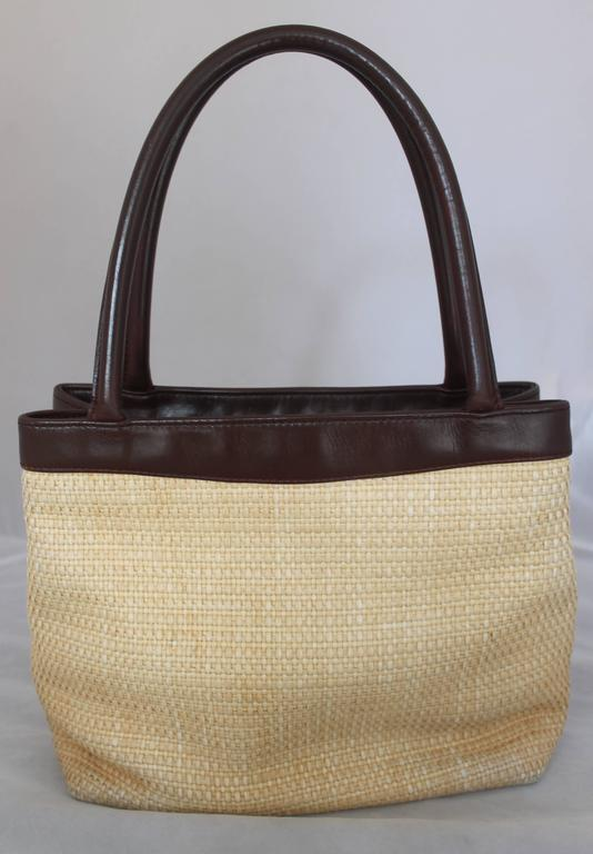 "Chanel Raffia Small Tote w/ Brown Leather Trim w/ ""CC"" Logo - Circa 2000-2002.  This beautiful Chanel tote is in very good condition with only a slight snag in the front.  It features a perfect summer and/or day time raffia material, a ""CC"" logo"