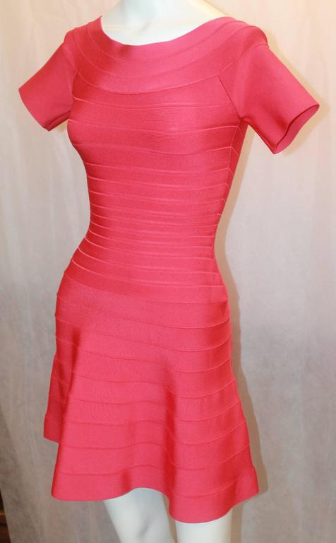 Herve Leger Raspberry Stretch Short Sleeve Dress - XS. This dress is in impeccable condition and is perfect for a night out. The neck has a round look and the skirt on the bottom flares out. The dress also has the pleated look all