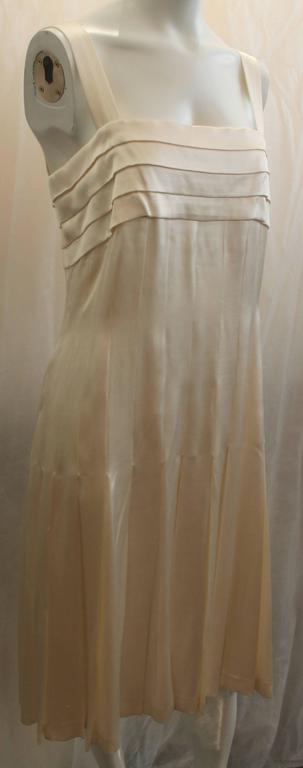 Chanel Ivory Silk Pleated Flapper Inspired Dress - 40 - 05P. This dress is a beautiful piece and is in fair condition due to some pulling throughout the garment, a couple snaps missing on the back end, and a very faint spot near the front. This