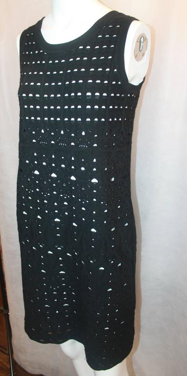 Chanel Black Crochet Sleeveless Shift Dress with White Underlay - 38. This dress is excellent condition with a small area of crochet loose on the left. The material is heavy and synthetic and creates a stunning look.  Measurements: Bust-