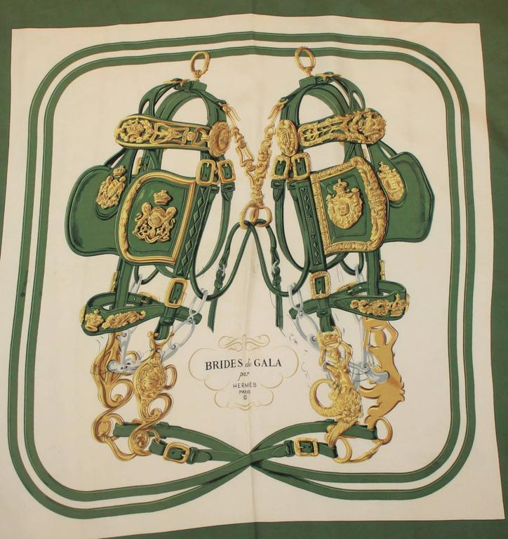"""Hermes Green, Gold, & Ivory """"Brides de Gala"""" Silk Scarf.  This lovely scarf is in excellent condition.  It features a lovely green, gold, and ivory """"Brides de Gala"""" theme with a horse bridle with blinders design.  This is the perfect"""