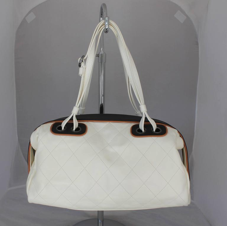 Chanel White and Black with Brown Trim Quilted Lambskin Shoulder Bag. This white shoulder bag is quilted lambskin and has a black and tan trim and palladium hardware. The flaps can come out and the black top can be tucked in. There is a