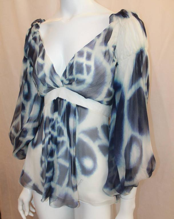 Roberto Cavalli Blue & White Printed Silk Chiffon Blouse - 38. This flowing blouse is in excellent condition and has a watercolor-like print. This top features a plunging neckline, puffy sleeves, and a mesh waist section.