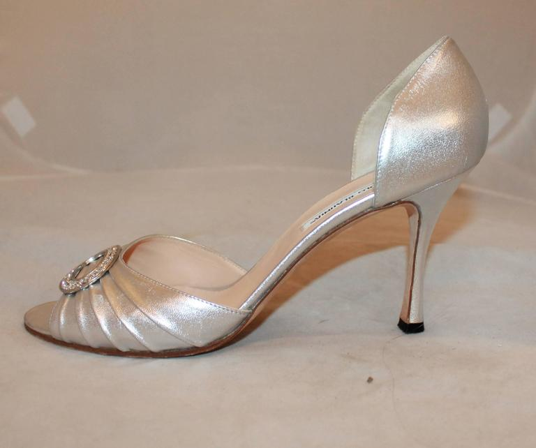 Manolo Blahnik Metallic Silver Leather Heels with Rhinestone Buckle - 41.5. These open-toe heels are a metallic silver and have cinching. They also have a rhinestone-encrusted buckle on the front. They are in good condition and show some scuffs on